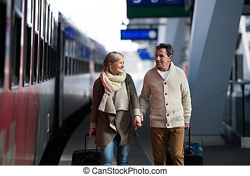 Senior couple on train station pulling trolley luggage. -...