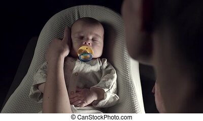 The child is sleeping with a pacifier in his mouth in a cot....