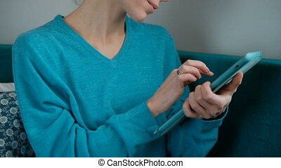 Young woman in a turquoise sweater Leafs tablet on a green...