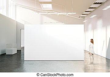 Woman walking near blank white wall mockup in modern...