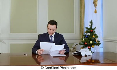 Businessman reading and signing documents sitting by table...