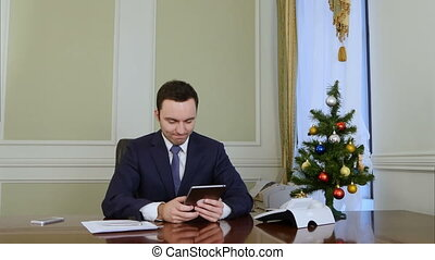 Successfull businessman using a tablet to send E-mail...