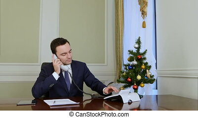 Smiling businessman picking up the phone and congratulates business colleagues with Christmas
