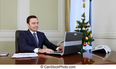 Young businessman has video calling on his computer in the...