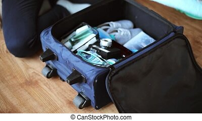 hands packing travel bag with personal stuff - tourism,...