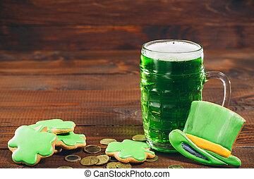 Beautiful background for St. Patrick's day with a glass of green beer, gold coins and hat on wooden table. Free space