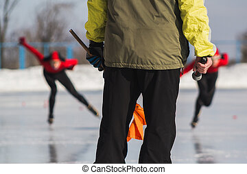 Speed skating competition - instructor and sportsmen on ice...