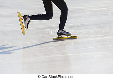 Golden skates at ice rink - winter sport concept, telephoto...