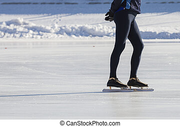 Man's legs on skates ice ring - winter sport at sunny day,...