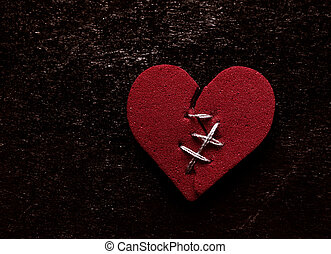 Broken hearted - Broken red heart with thread stitches on...
