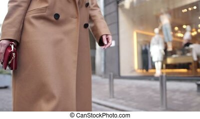 Woman holding red clutch while walking on street