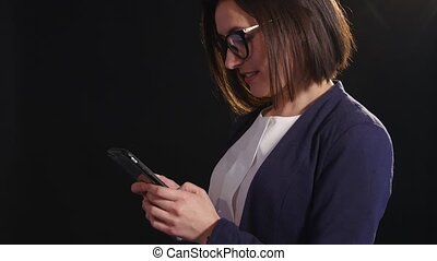 young professional woman browsing the internet or texting on her cell phone phone over dark background