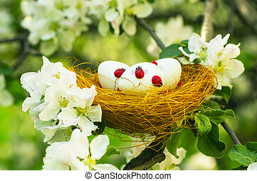 Easter eggs in a nest in the flowering garden