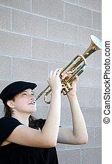 Female trumpet player blowing her horn outside.