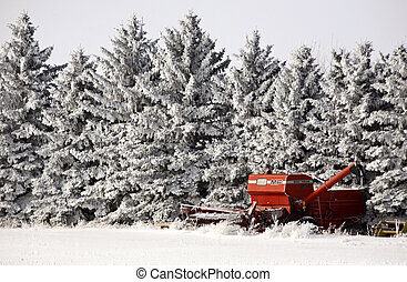 Old combine next to hoar frost covered trees in winter -...