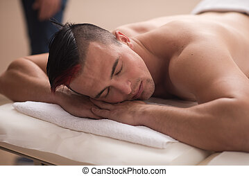 handsome man resting in a spa massage center