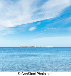 blue sea and sky with clouds. island on horizon