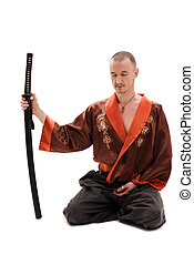 Man in traditional chinese in studio with a sword - Man in...