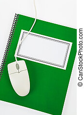 Green school textbook and computer mouse