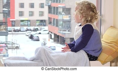 Curious child looking at snow fall through window in winter