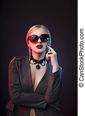 Glamorous blonde lady in glasses with bright makeup