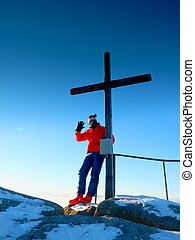 Man hiker in warm clothes on summit with wooden cross. - Man...