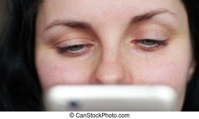 close-up of woman eye looking smartphone - Young beautiful...