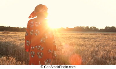 African woman in traditional clothes standing in a field of...