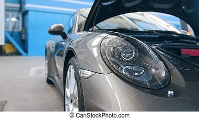Automobile garage - luxury sport car standing for checking...