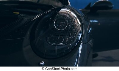 Close up view of headlights of luxury sport car - auto...