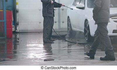 Car wash - worker in auto service is washing a car in the suds by water hoses