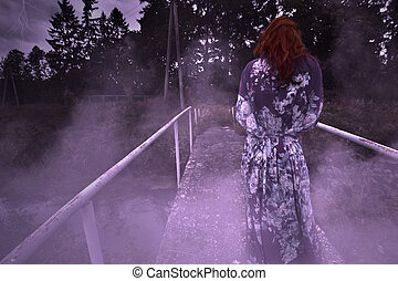 A terrible sinister woman is standing on the bridge at night in a fog
