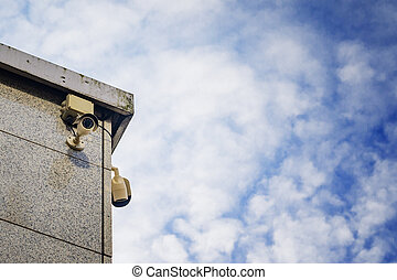 Two Security cameras on the side of an modern building