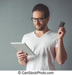 Man doing shopping online - Handsome man is holding a...