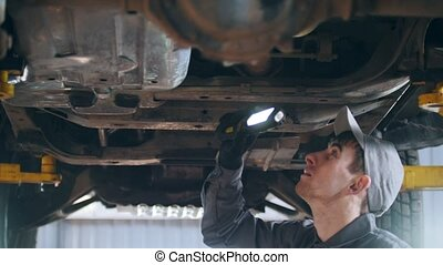 Mechanic is checking the bottom of car in garage automobile service, close up