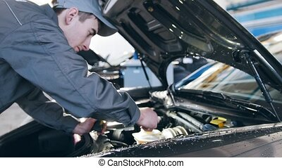 Mechanic in overalls working in the garage - repairing luxury sportcar