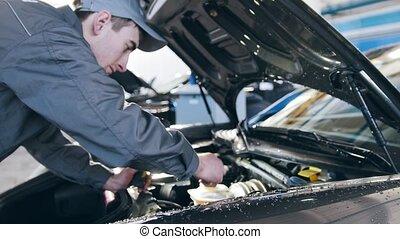 Mechanic in overalls working in the garage - repairing...