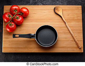 Frying pan nd tomatoe on a wooden board