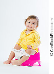 Little smiling girl sitting on a pot. Isolated on white background.