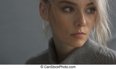 Face of woman looking away - Close-up of woman wearing gray...