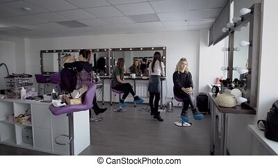 Professional hair stylist and makeup artist in their large studio preparing models before going on the podium for the show. Beautiful girl admires itself in a mirror and then looks in the smartphone.