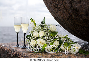 wedding bouquet and two champagne glasses outdoors