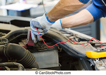 auto mechanic man with multimeter testing battery - car...