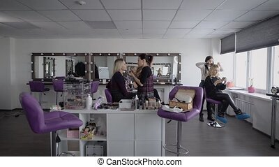 The camera moves in a spacious room where makeup artists...