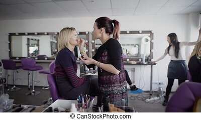 Make-up artist is working preparing model for future shooting. Brunette female master is applying cosmetics on client's face while hairdresser is finishing hairdo for blonde woman in the background.