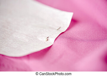 paper pattern attached with sewing pin to cloth - needlework...
