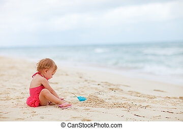 Toddler girl playing with sand