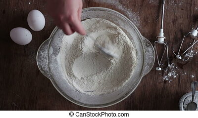 Top view of hands stirred the flour with a spoon. - Top view...