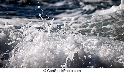Sea Foam - Detail of ocean waters splashing on to a rocky...