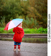Toddler girl with umbrella - Back view of toddler girl with...